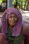 An old woman sits at a table. Angkor Wat, Siem Reap, Cambodia.