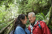 Senior man and middle-aged woman in forest looking in eyes smiling
