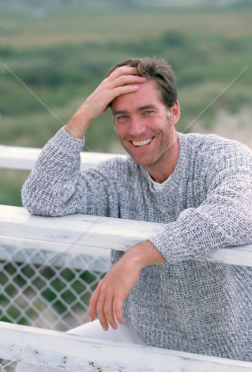 Good looking man smiling and leaning on a fence in Amagansett, NY