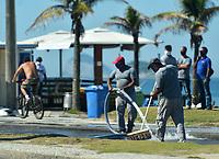 Rio de Janeiro-Brazil12 May 2020 Workers wash the boardwalk at Barra da Tijuca beach during the coronavirus pandemic (COVID19)