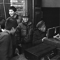 SHAANXI PROVINCE ,24 DECEMBER 2000: children watch a church helper repairing a loud speaker for the upcoming Christmas mass. China cut relations with the vatican in the early fifites and since then, established a Patriotic catholic Church that's controlled by Chinese authorities.<br />