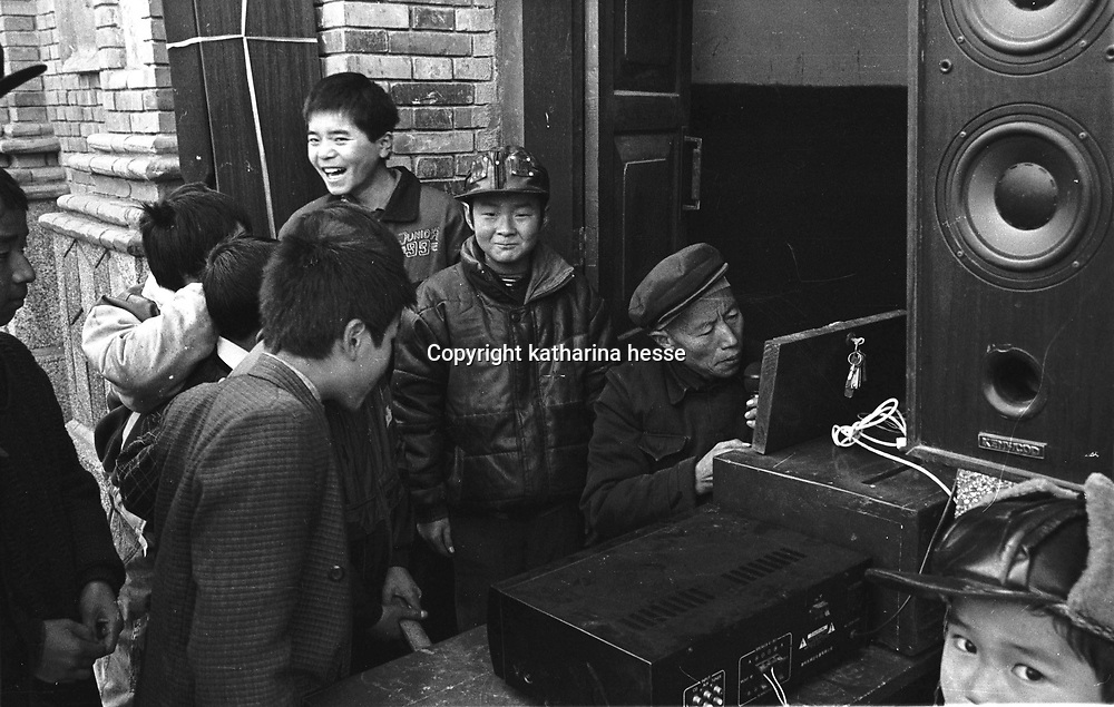 SHAANXI PROVINCE ,24 DECEMBER 2000: children watch a church helper repairing a loud speaker for the upcoming Christmas mass. China cut relations with the vatican in the early fifites and since then, established a Patriotic catholic Church that's controlled by Chinese authorities.<br />Catholics who refused to give up their ties with the Vatican, started worshipping in underground churches and consequently were persecuted for a long time. Since the late nineties though, relations with the vatican informally started to improve. Although China still has no diplomatic relations, many representatives from official churches met the pope John Paull II secretely . Since the pope's death on Saturday, thousands of catholics commemorate John Paull II  in special masses throughout China.