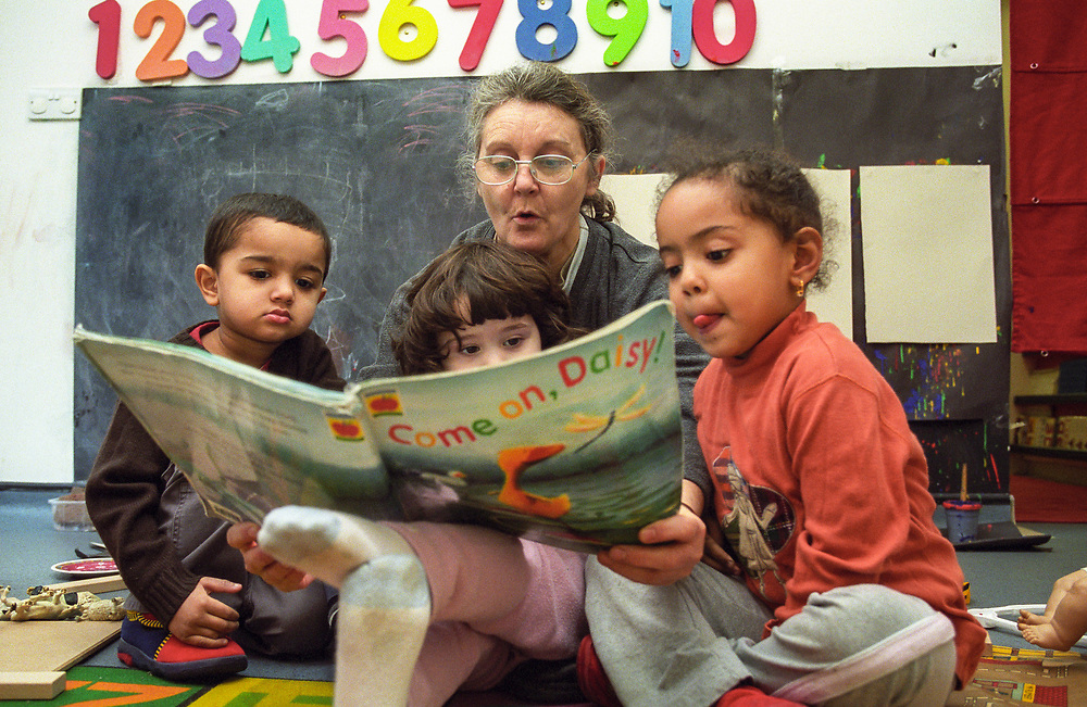 Teacher reading to a group of children at a nursery school