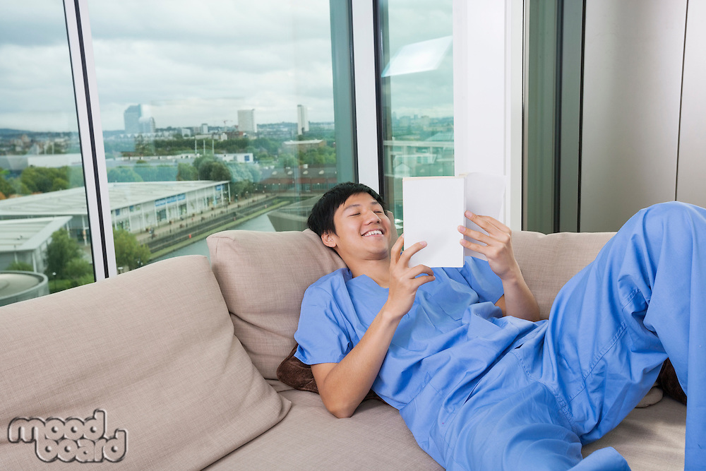 Happy mid adult man reading book while lying on sofa by window