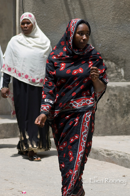 Women wearing colourful headscarves walking in Stone Town, Zanzibar,<br /> Tanzania
