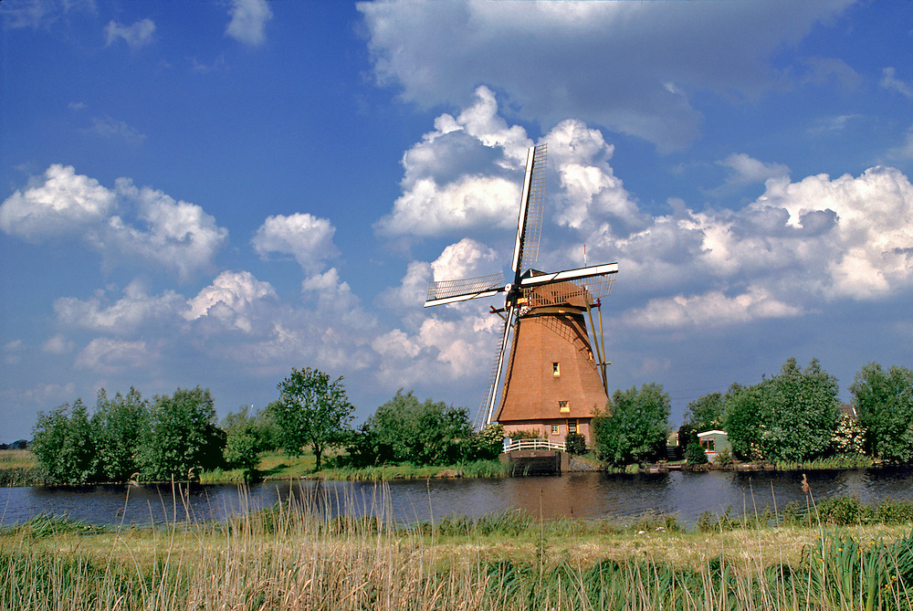 A windmill sits on the edge of the canal,  at Kinderdijk, Netherlands.