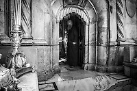 A Greek Orthodox monk stands at the entrance to the Edicule, or tomb of Jesus, inside the Church of the Holy Sepulchre in Jerusalem