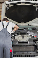 Rear view of male engineer repairing car in automobile repair shop