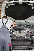 Rear view of male engineer repairing car in automobile repair shop