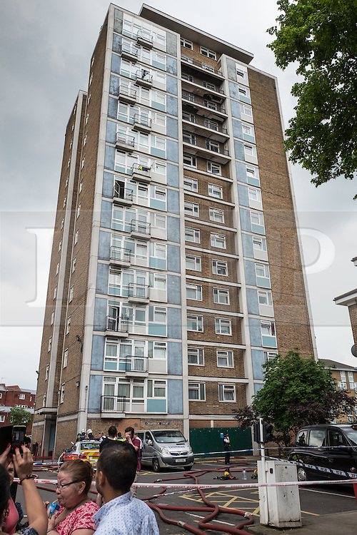 © Licensed to London News Pictures. 11/06/2016. London, UK. Local residents gather as fire crews and paramedics work after a large fire broke out in a tower block on Canterbury Crescent in Brixton, south London. Plumes of smoke could be seen from across south London, and some on Twitter also reported hearing an explosion. Photo credit: Rob Pinney/LNP