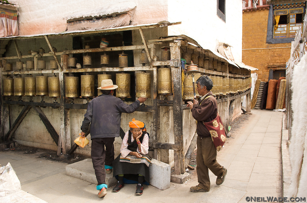Tibetan men spin prayer wheels around a small temple oon the Barkor in Lhasa, Tibet.