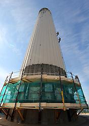 Image ©Licensed to i-Images Picture Agency. 02/07/2014. London, United Kingdom. Steeplejacks check the south west chimney of  Battersea Power Station before the first stage of its dismantling begins later this month. All four chimneys of the power station are being rebuilt as part of the re-development of the site. Picture by Stephen Lock / i-Images