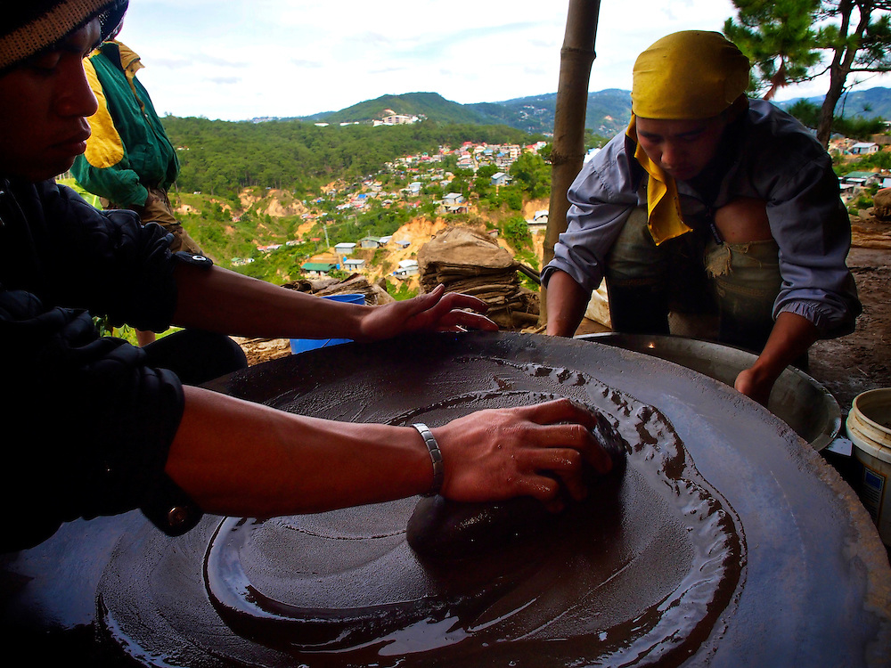 Mine workers in the Emerald Mountain mining area just outside Baguio, a large city on northern Luzon Island, use an environmentally progressive method to extract gold from ore.  Instead of mercury, miners use cyanide and borax to process ore.  The process is more labor intensive, however.  Cyanide is highly poisonous and the byproducts of gold processing can harm the environment but is considered more environmentally friendly than using mercury...On Emerald Mountain, miners extract ore with picks and hammers and load the ore into small carts.  Ore sacks are stacked for tumbling into fine particles which are then mixed with cyanide crystals to form gold cyanide, a compound that can reduced by treatment with sulfuric acid.  Further panning and separation reveals low-grade gold particles suspended in a dense mud.  This is treated with borax, heated in a crude blast furnace to reveal higher-grade gold...Photos show the ore tumblers,  cyanide-laced sludge, Sodium Cyanide pellets on top of ore sacks and miners at work panning.  Other miners work inside Emerald Mine...After the panning process, a miner wraps a ball of processed sludge in a small plastic bag doused with borax.  The bag is placed in a high intensity charcoal furnace fed with forced air to achieve higher temperatures.  After about 20 minutes, byproducts are evaporated revealing the pure gold. ..A miner displays a nugget worth about $2100.  After giving the landowner a 70 percent share of the gold production and splitting the remainder, a typical small-scale miner makes about $30. per day...Story Summary:.Small-scale gold mining in the Philippines uses mercury and cyanide to extract elemental gold from ore extracted from mines and pits dug by hand.  Very young children, some as young as four, are put to work at less dangerous but still rigorous tasks in the gold mining areas.  These include panning in streams or rivers and hauling ore sacks that can weigh up to 60 pounds.  Children often play near mechanized e