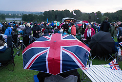 © Licensed to London News Pictures.22/08/15<br /> Castle Howard, North Yorkshire, UK. <br /> <br /> A woman sits under a Union Flag umbrella during a rainstorm as hundreds of people attend the 25th anniversary of the Castle Howard Proms event near York. The theme of the event this year is a commemoration of the 75th anniversary of the Battle of Britain and the 70th anniversary of VE day and brings an evening of classic musical favourites celebrating Britishness to the lawns of Castle Howard.<br /> <br /> Photo credit : Ian Forsyth/LNP