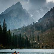 Brian Bishop kayaks at dusk in String Lake in Grand Teton National Park, Wyoming