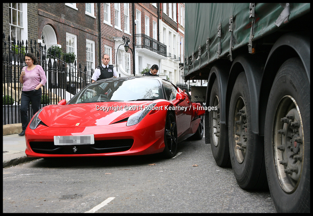 This unlucky Ferrari owner is going to get a shock when he comes to find an articulated lorry wedged in the side of his car. The incident happened in Kensington Square, London, United Kingdom. Monday, 10th March 2014. Picture by Robert Kearney / i-Images