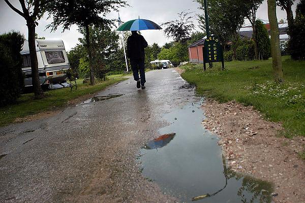 Nederland, Groebeek, 11-7-2004Camping de oude molen in Groebeek heeft een troosteloze aanblik door de regenbuien die regelmatig vielen dit weekeind. Vakantie, regen, natte zomer, recreatie, parapluie, kamping, kamperen, recreatie.Foto: Flip Franssen/Hollandse Hoogte