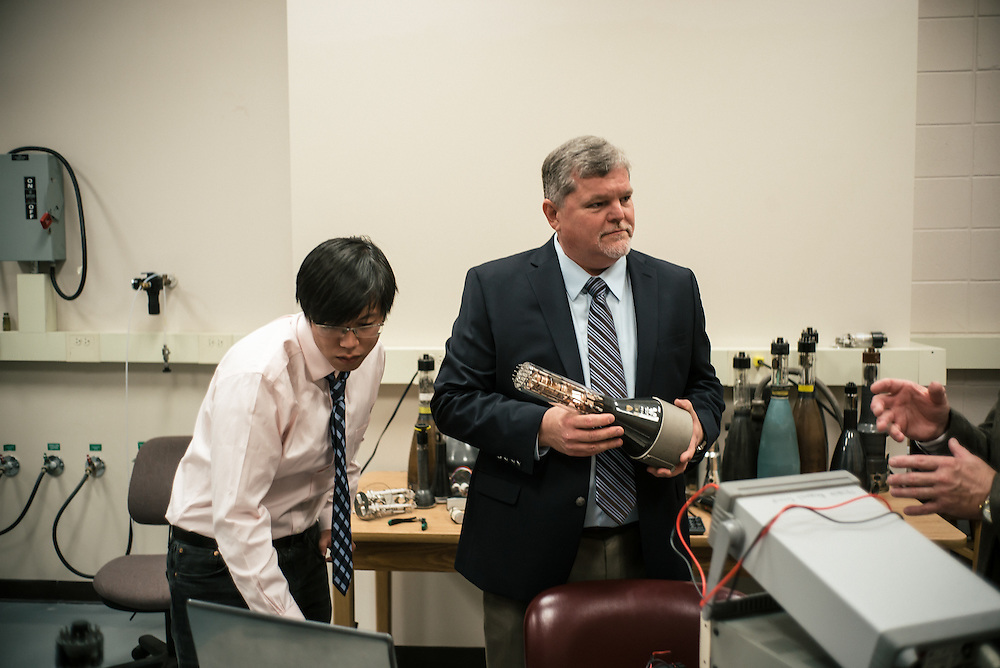 "AUBURN, AL – NOVEMBER 20, 2016: Yan Chen (left) and Bart Prorok (center), examine antique cathode ray tubes from television sets for use in an additive manufacturing experiment. In 2016, Auburn University received a grant to develop low cost additive manufacturing techniques, which would allow small businesses interested in additive manufacturing to cheaply test the method's viability for their unique production needs. By repurposing the infrastructure inside cathode ray tubes, the existing electron gun inside the tubes is harnessed for additive manufacturing. ""All the infrastructure used in the million dollar machines is right here in these tubes,"" Prorok said. ""It's more crude, and tuned to a different application, but it's there. We're trying to harness them to do something new."" Prorok believes the method has potential to become the new paradigm for how newer additive manufacturing machines are built.<br /> <br /> In much of the United States, global trade and technological innovation has failed to produce the prosperity hoped for by political and business leaders. Yet despite formidable economic challenges, some localities are flourishing. In Lee County, Ala., unemployment is below the national average despite the loss of thousands of manufacturing jobs, and the key to the county's resilience may be Auburn University, which provided a steady source of employment during recessions and helped draw new businesses to replace those that fled. CREDIT: Bob Miller for The Wall Street Journal<br /> [RESILIENT]"