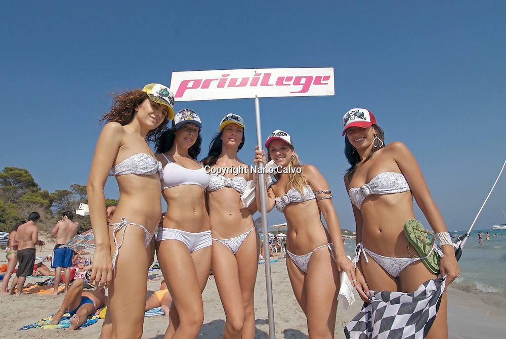 Sexy attractive young girls in white bikinis doing promotion of Privilege club , the biggest in the world, in Salinas beach, Ibiza, Spain - Photo by Nano Calvo