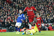 Liverpool forward Sadio Mane (10) goes round Everton goalkeeper Jordan Pickford (1)  during the Premier League match between Liverpool and Everton at Anfield, Liverpool, England on 4 December 2019.