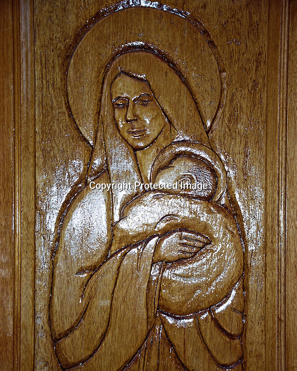 "Carved image of the Virgin Mary on wooden door. NOTE: Click ""Shopping Cart"" icon for available sizes and prices. If a ""Purchase this image"" screen opens, click arrow on it. Doing so does not constitute making a purchase. To purchase, additional steps are required."