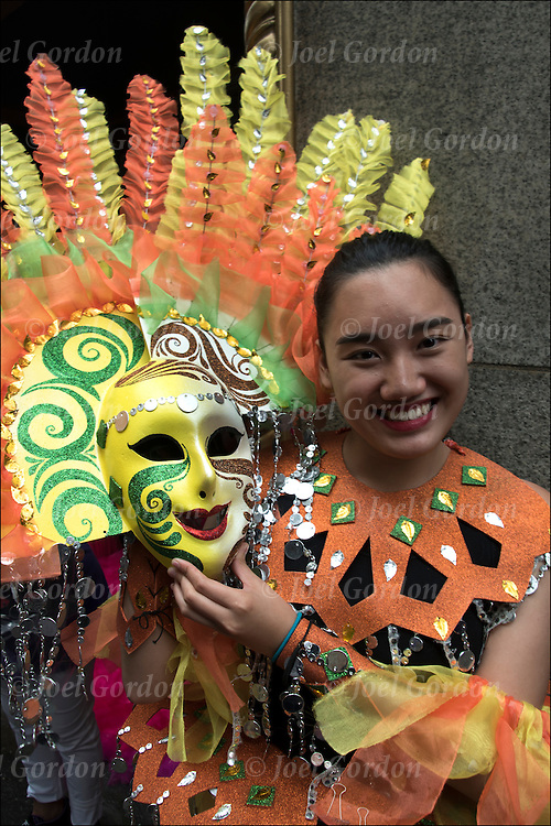 "Second generation young adult looking into the camera holding her traditional ""Masskara"" mask.  She is one of the many faces in the Philippine Independence Day Parade in NYC."