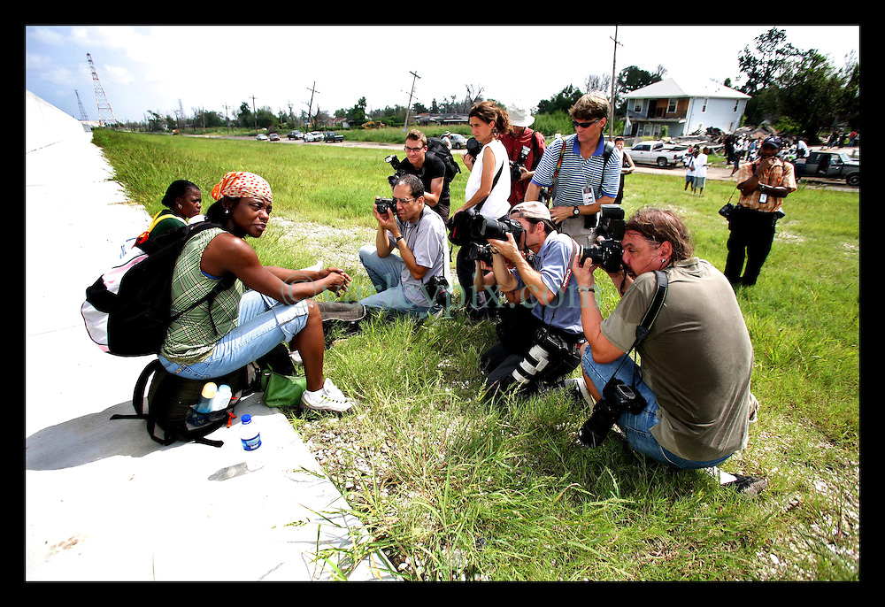 29 August 2006 - New Orleans - Louisiana. Lower 9th ward. The media swarm like vultures around a woman sat crying beside the newly renovated industrial canal levee flood wall. Civilians gathered at the site of the breach of the industrial canal for the Great Flood commemoration and memorial ceremony to 'honor and remember our loved ones who have passed.' People came to mark the anniversary of devastating hurricane Katrina at the site where the now repaired and allegedly in theory stronger levee flood wall. The levee breached along the industrial canal at the point where people gathered, needlessly killing hundreds of innocent civilians in the worst engineering disaster in US history.