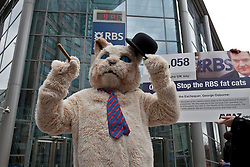 © Licensed to London News Pictures. 25/01/2012. London, U.K..Avaaz fat cat protest outside The Royal Bank of Scotland(RBS) in Bishopsgate, London. RBS is expected to meet to decide how much to pay its investment bankers, including chief executive Stephen Hester. More than 90,000 people have signed an Avaaz petition calling on the government to stop million-dollar bonuses being paid to RBS bosses. Protesters with placards and a fat cat costume joined the protest. Photo credit : Rich Bowen/LNP