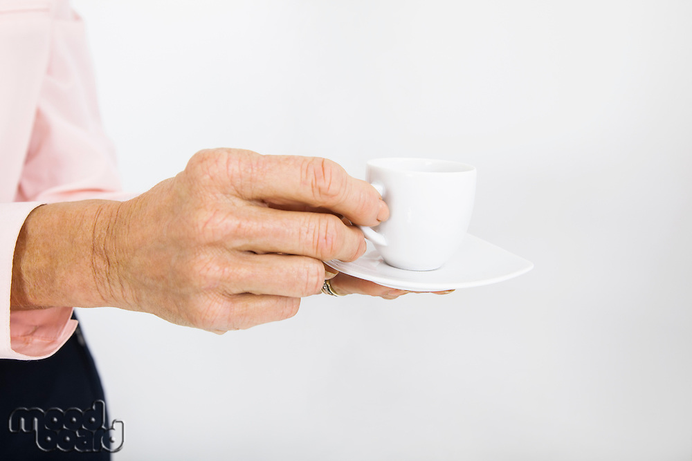 Cropped image of senior businesswoman with espresso cup at office