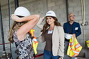 Paula Millard of Synergy Global Housing checks her hard hat with a colleague before staring a tour during SVBJ's BizMix presented by SWENSON at The Grad in Downtown San Jose, California, on July 31, 2019. (Stan Olszewski for Silicon Valley Business Journal)