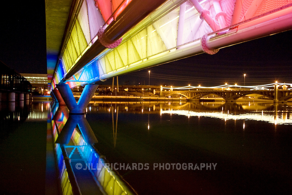 The Metro Light Rail and its 20 mile of rail line serves Phoenix, Tempe and parts of Mesa. It has been in operation since 2008 and has eased the congestion of traffic in downtown Phoenix, Arizona. Bright light illuminates the rail bridge over Tempe Town Lake in Tempe, Arizona.