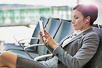 Portrait of young attractive businesswoman using digital tablet with earphones on while waiting for boarding in airport with lens flare