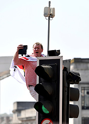 A Wolverhampton Wanderers supporter climbs on top of a traffic light to get a better view during the winner's parade through Wolverhampton.