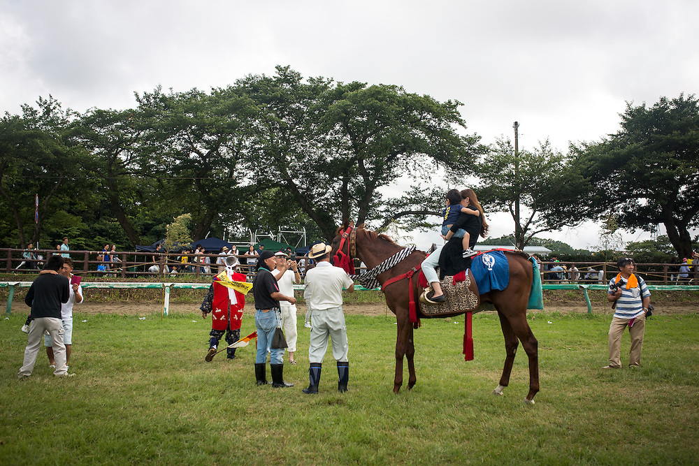 """MINAMISOMA, JAPAN - JULY 24 :  A family of samurai try to ride the horse for photo after the Soma Nomaoi festival at Hibarigahara field on Sunday, July 24, 2016 in Minamisoma, Fukushima Prefecture, Japan. """"Soma-Nomaoi"""" is a three day traditional festival that recreates a samurai battle scene from more than 1,000 years ago. The festival has gathered more than thousands visitors as Fukushima still continues to recovery from the 2011 nuclear disaster, the samurai warriors battles for recovery of the area. (Photo: Richard Atrero de Guzman/NURPhoto)"""