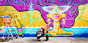 Artist Claudia LaBianca spray-painting a  mural at a vintage sthrift shop in Miami's Wynwood arts district.