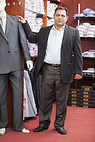 Portrait of businessman standing by mannequin dressed in suit at menswear store