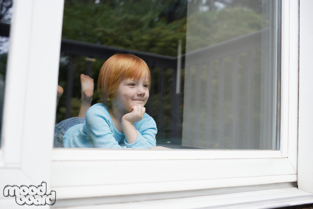 Young girl (5-6) indoors looking through window