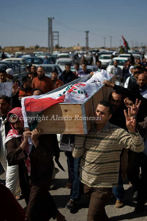 LIBYA, ADJABIYA. Rebels carry the coffin of one fallen comrade, killed during heavy fightings in Brega the day before, on March 03, 2011. ALESSIO ROMENZI
