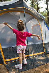 A young girl celebrates camping in front of her tent at the North of Highland Campground near the Cape Cod National Seashore in Truro, Massachusetts.