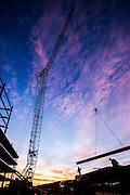 crane hoistinf a steel beam at a construction site