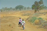 Two men cycling the deserted road to Sebba, Burkina Faso (formerly Upper Volta)