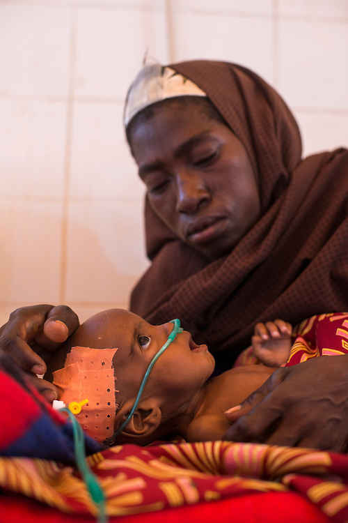 A mother sits with her severely malnourished and ill child who is receiving a blood transfusion in the intensive care unit of the Save The Children malnutrition clinic at the Aguie hospital in the Maradi region of southern Niger. Located in the Western Sahel, the landlocked country suffers from chronic malnutrition and food insecurity caused by climate related drought and erratic rainy seasons, inadequate arable land, one of the highest demographic growth rates in the world, poor social and sanitary living conditions and widespread poverty. Food insecurity affects children under five and women disproportionately, especially in rural areas. Aguie, Niger. 15/07/2017.