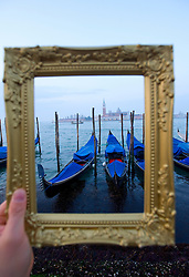 Grand Canal and gondolas at dawn framed within picture frame in Venice Italy