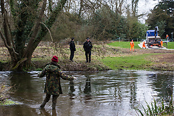 Denham, UK. 4 February, 2020. An environmental activist from Extinction Rebellion liaises with police officers monitoring works for the HS2 high-speed rail link adjacent to the river Colne in Denham Country Park. Planned works are believed to include the felling of 200 trees and the construction of a roadway, Bailey bridge, compounds, fencing and a parking area. The near side of the river lies within a wetland nature reserve forming part of a Site of Metropolitan Importance for Nature Conservation (SMI). Credit: Mark Kerrison/Alamy Live News