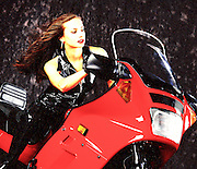 "A beautiful young woman in a black catsuit astride a red sport motorcycle. -- To determine pricing and license this image simply click ""Add To Cart"" below --"