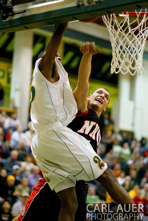 1/13/2006: Senior guard Eric Draper (25) of the UAA Seawolves heads up hard to the hoop to attempt a dunk as he is fouled by Tim Ireland of the Northwest Nazarene University Crusaders in the Alaska Anchorage comeback victory over Northwest Nazarene, 60-57, in men?s basketball action at the Wells Fargo Sports Complex on Saturday.