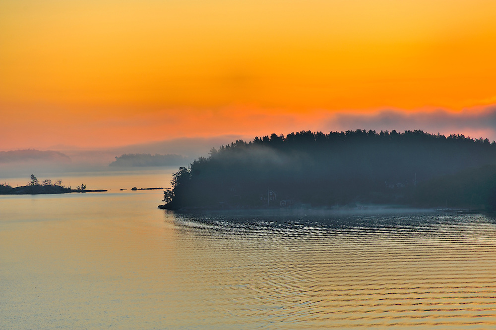 The Stockholm Archipelago along the Swedish coastline seen from the Baltic Sea just as the white night ended and a golden sunrise which would lated turn to pink and purple began. Cottages are just visible in the fog.