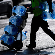 February 17, 2015 - New York, NY : A worker carts empty blue Poland Spring water jugs across Amsterdam Ave. near West 77th Street in Manhattan on Tuesday afternoon. CREDIT: Karsten Moran for The New York Times