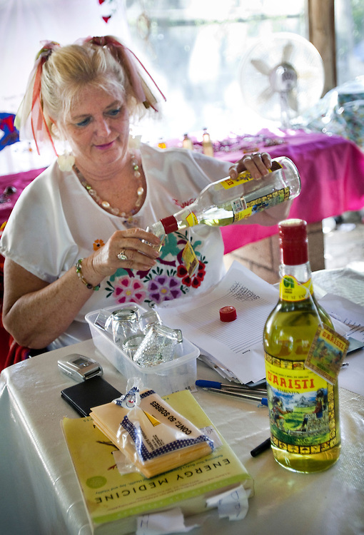Sandra Dayton serving her guests D'Aristi Xtabentun, a mayan liquor that helps them relax and is good for the stomach...The Jungle Spa in Puerto Morelos, Mexico, just 20 minutes from Cancun is managed by Sandra Dayton who is also the co-founder of the non-profit organization Lu'um K'aa Nab that helps mayan women make a living for them selves by selling handicraft and giving mayan massage at the Jungle Spa.