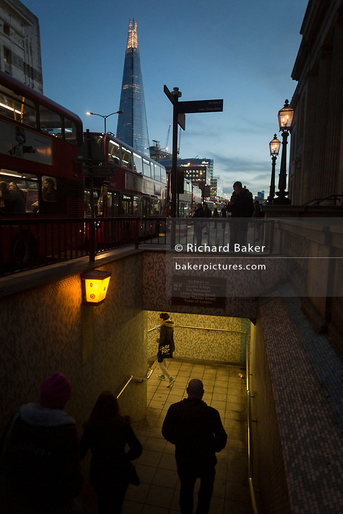 With the Shard in the background, pedestrians descend the steps of the tunnel under London Bridge during the evening rush-hour, on 8th November 2018, in London, England.